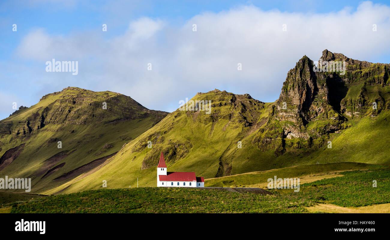 Église blanche avec un toit rouge sur une colline dans la région de Vik, Islande Photo Stock