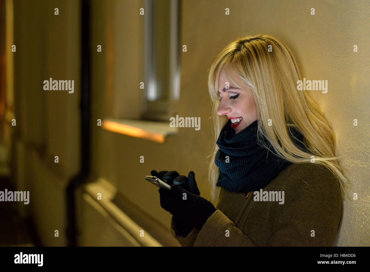 Smiling woman using smartphone à nuit Photo Stock