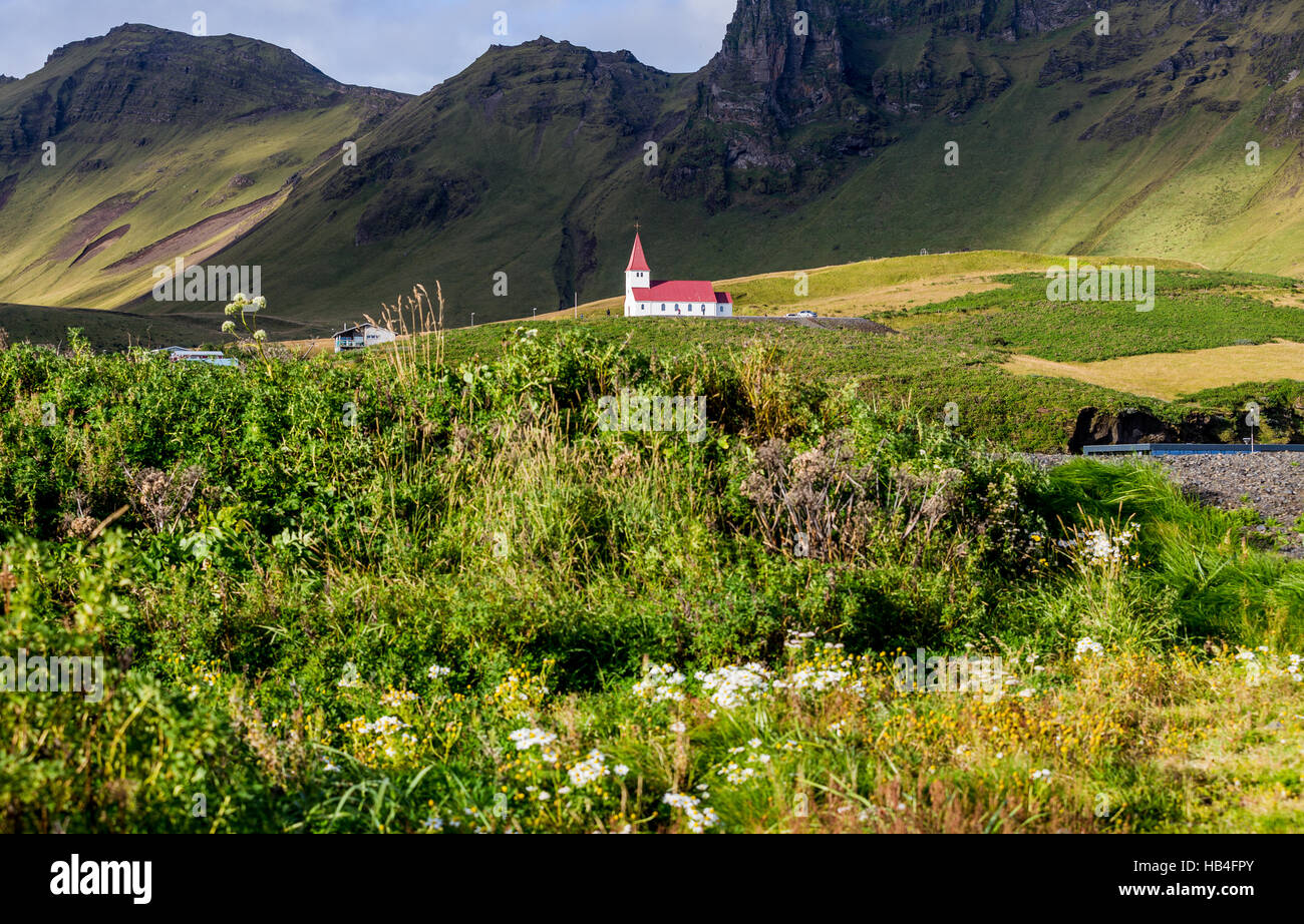 Église blanche au toit rouge sur une colline dans le sud de l'Islande. Photo Stock
