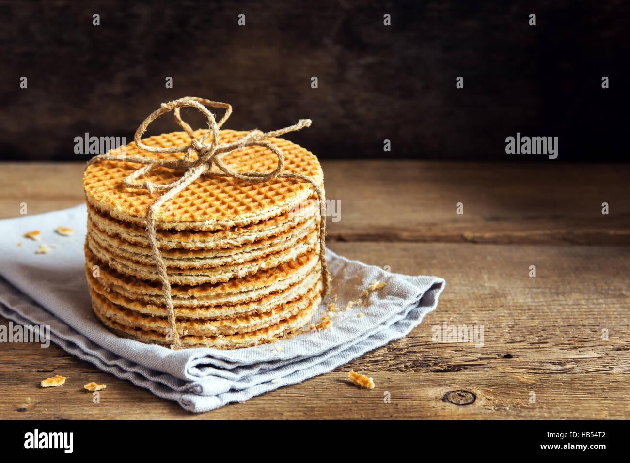 Pile de gaufres caramel traditionnel néerlandais attachés avec de la ficelle de jute sur fond de bois Photo Stock