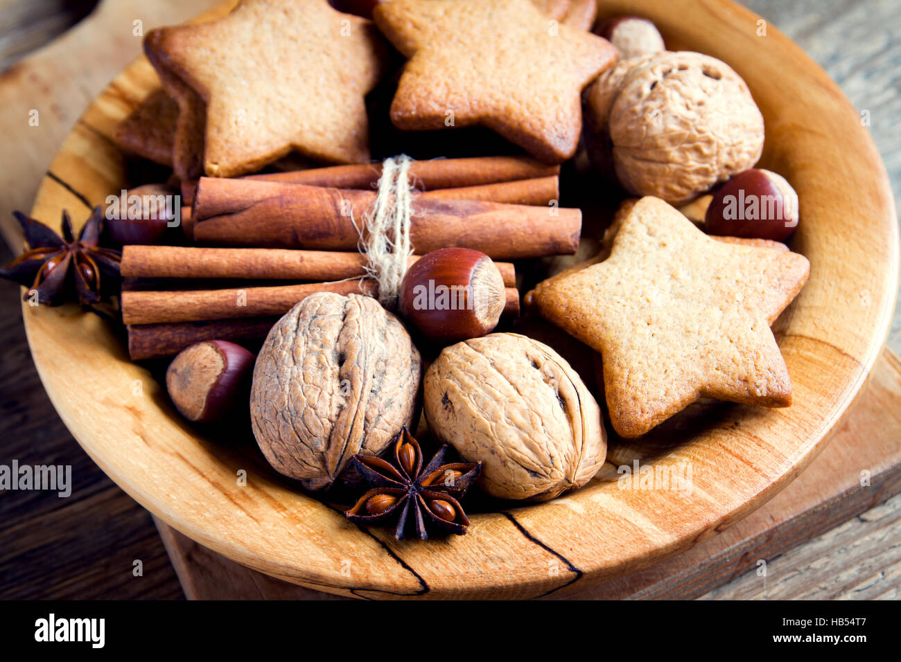 Noël décoration rustique avec gingerbread cookies, noix et épices de Noël sur plaque de bois Photo Stock