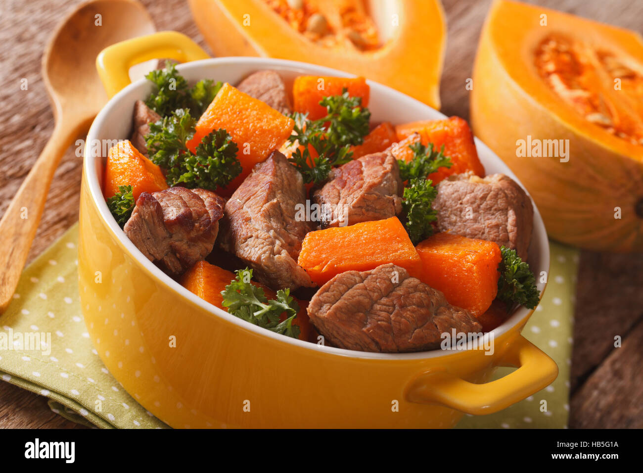 Cuisine maison: ragoût de boeuf à la citrouille libre dans le pot jaune sur la table horizontale. Photo Stock
