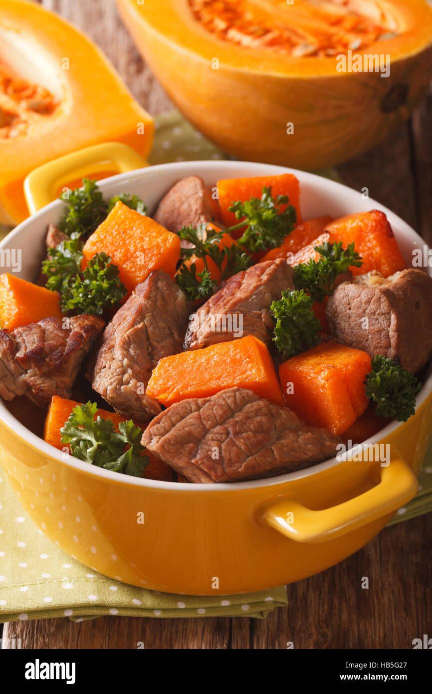 Ragoût de boeuf à la citrouille macro dans un pot sur la table verticale. Photo Stock