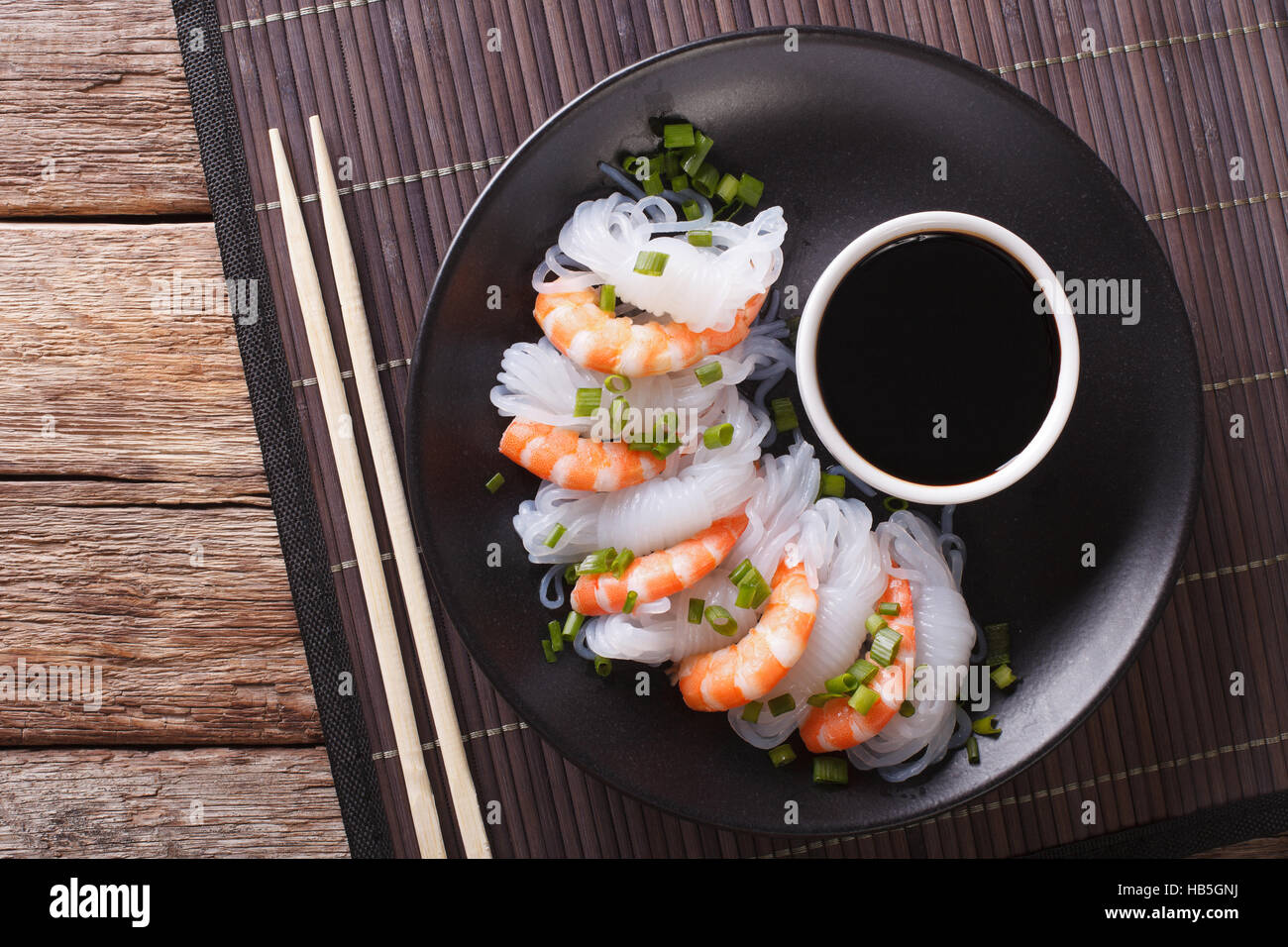 La nourriture japonaise: Shirataki aux gambas, oignons de printemps et de la sauce soja sur une assiette de Photo Stock