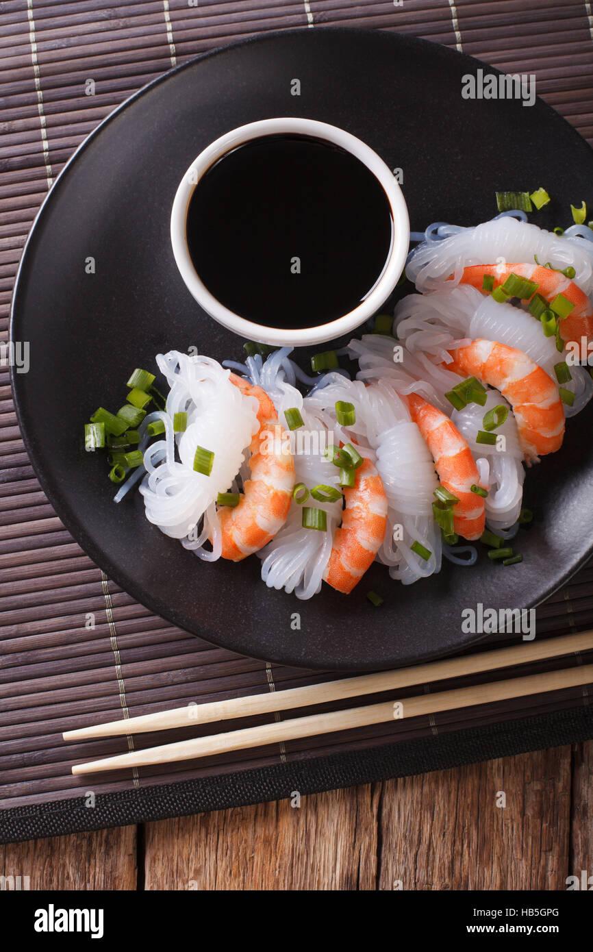 La nourriture japonaise: Shirataki aux gambas, oignons de printemps et de la sauce soja sur une plaque verticale. Photo Stock