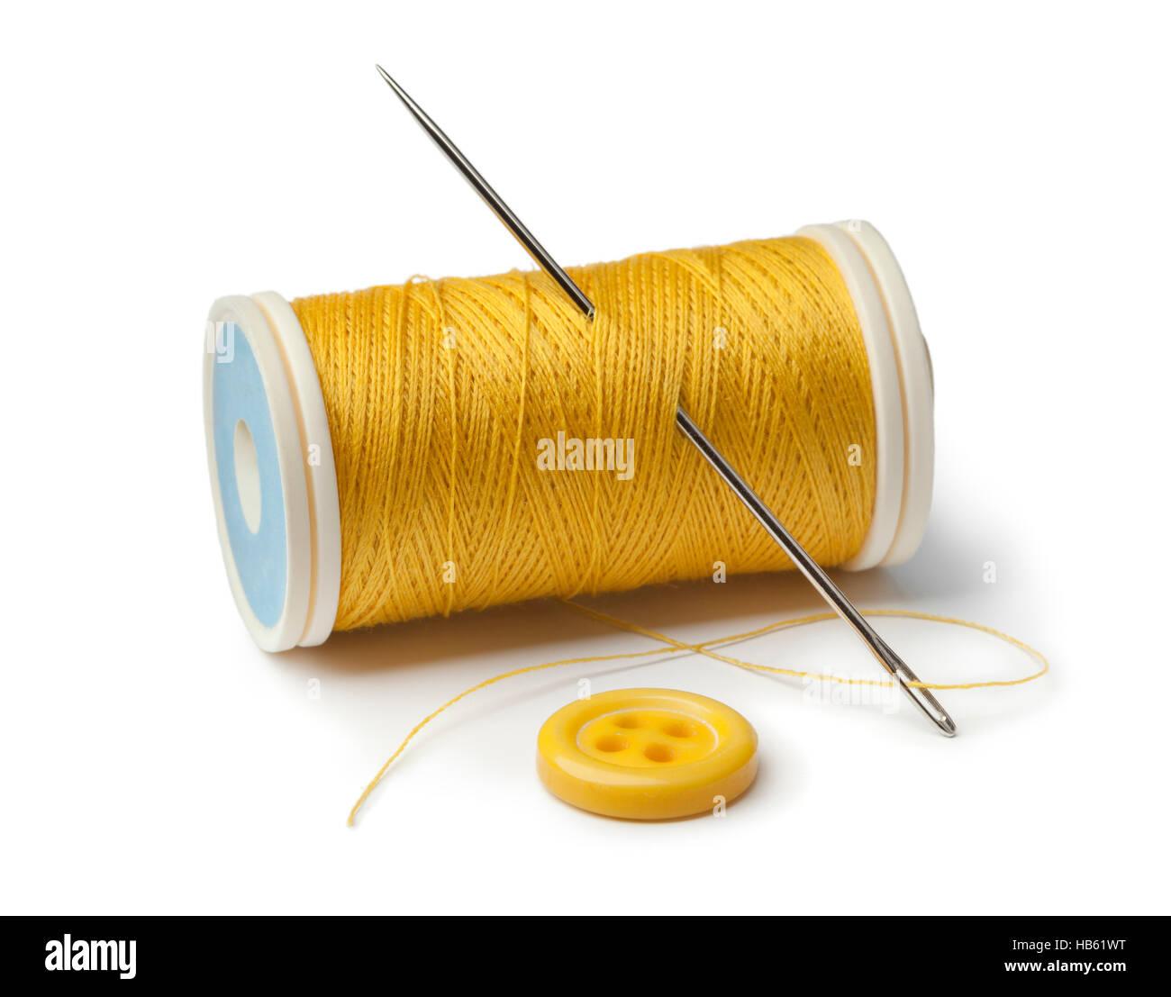 La canette jaune, l'aiguille et de couture bouton sur fond blanc Photo Stock