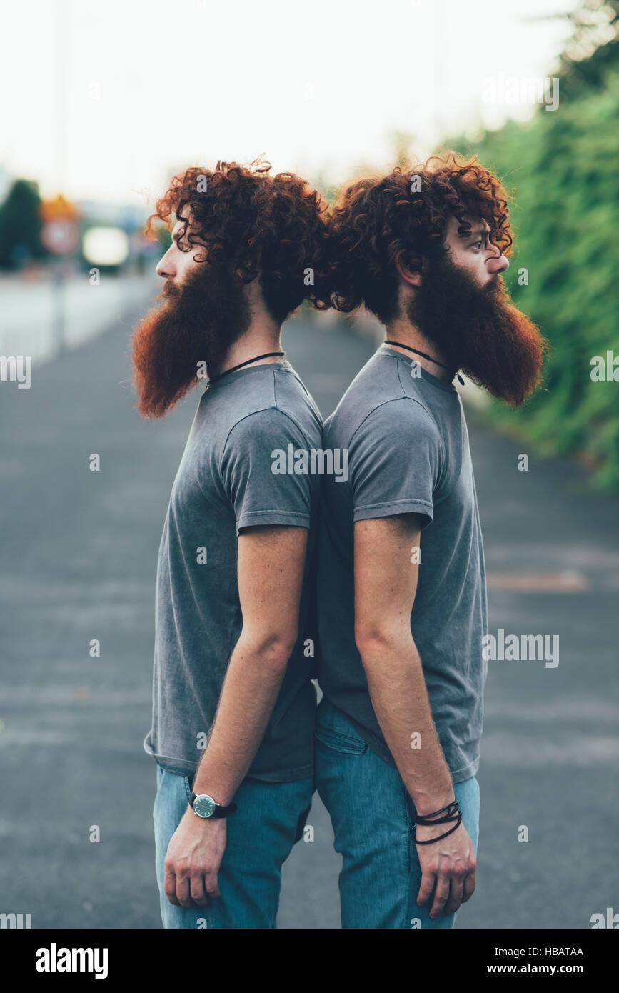 Portrait de jumeaux mâles adultes identiques aux cheveux rouges et barbes dos à dos sur le trottoir Photo Stock