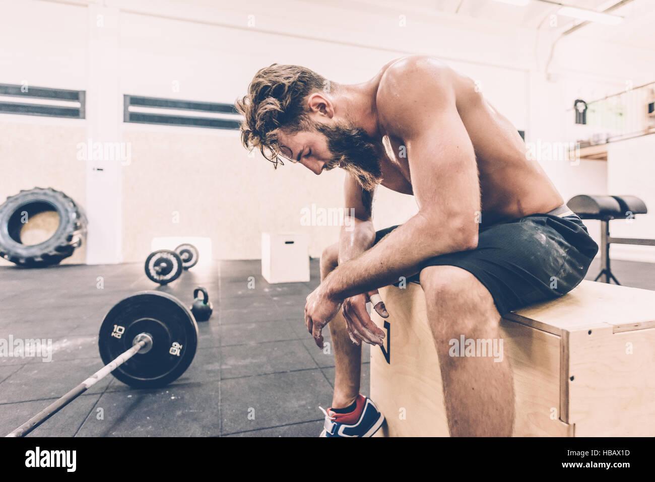 Épuisé homme cross trainer de prendre une pause de la salle de sport en haltérophilie Photo Stock