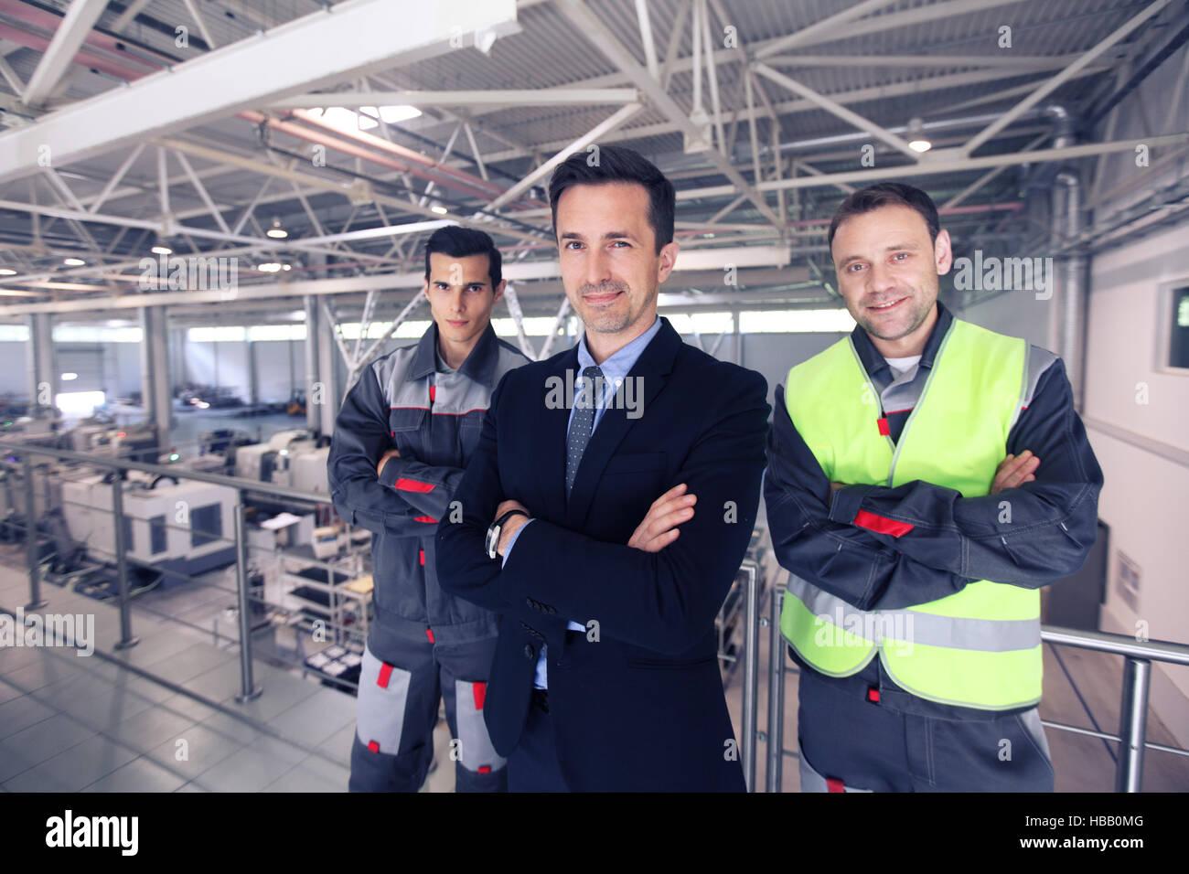 Équipe de manager et deux travailleurs en usine CNC Banque D'Images