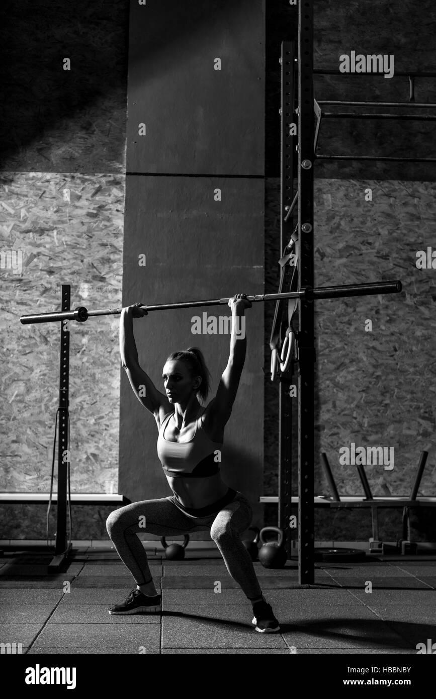 Athletic sporty woman squatting avec une longue barre en métal Photo Stock