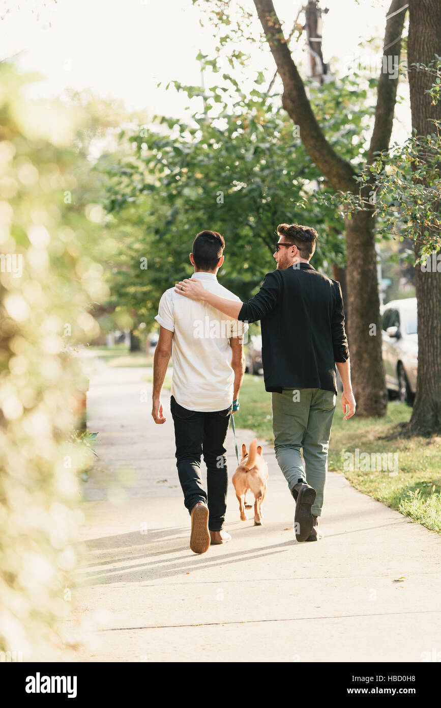 Vue arrière du jeune homme couple walking dog sur trottoir de banlieue Banque D'Images