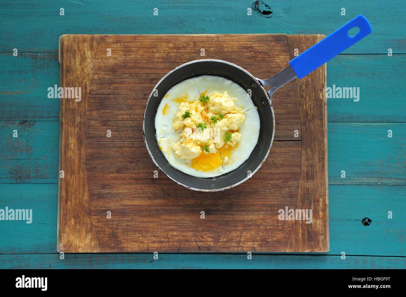 Mise à plat d'œufs brouillés dans un stylo. Texture de fond alimentaire. copy space Photo Stock