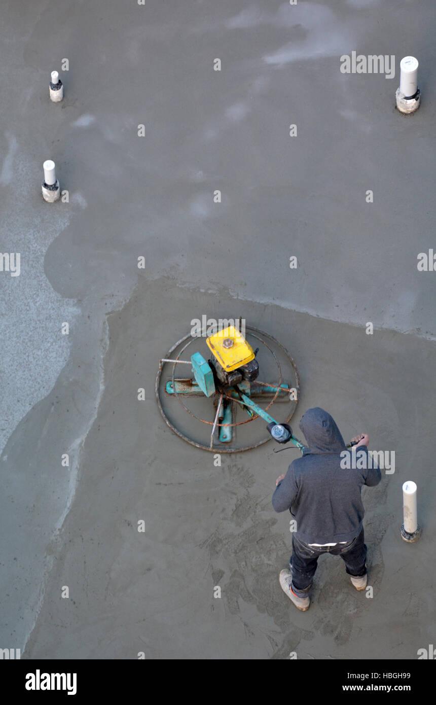 Les travailleurs du chantier de construction méconnaissable d'utilisation d'une truelle de lissage béton la machine sur un manteau de ciment dans la construction de site. Copy space Banque D'Images