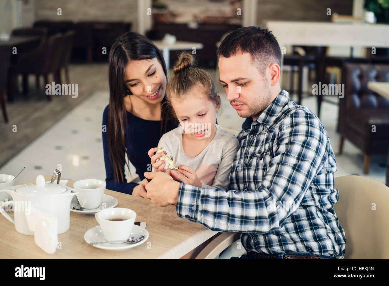 La famille, la parentalité, la technologie les gens heureux concept - mère, père et petite fille Photo Stock