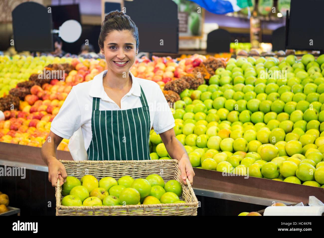 Le personnel de femme tenant un panier de pomme verte au supermarché Photo Stock
