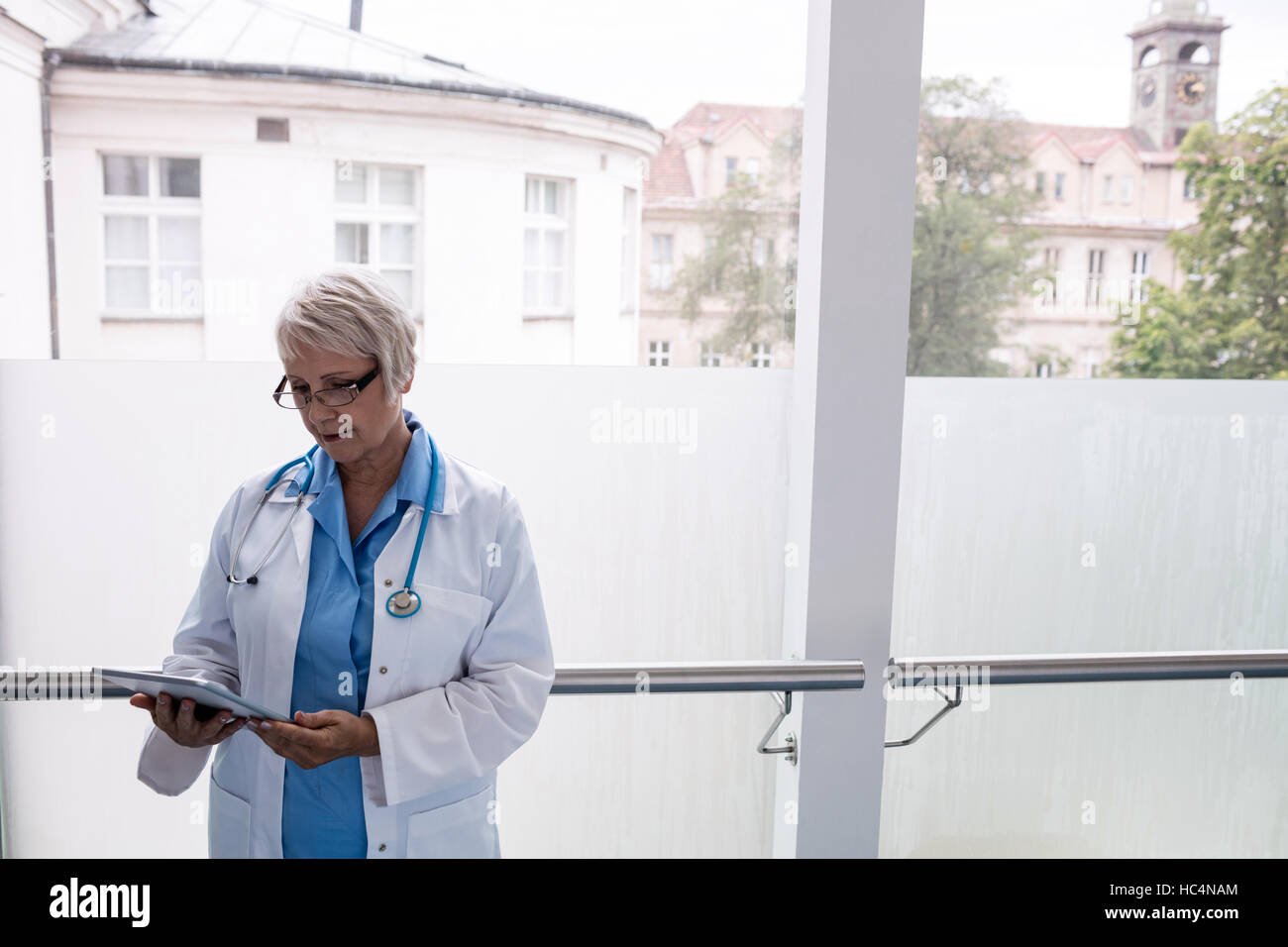 Doctor using digital tablet in corridor Banque D'Images