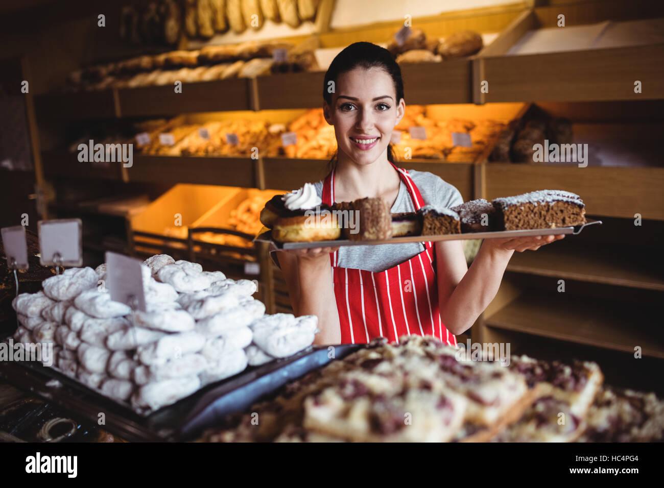 Portrait of female baker holding a tray de sucrés Photo Stock