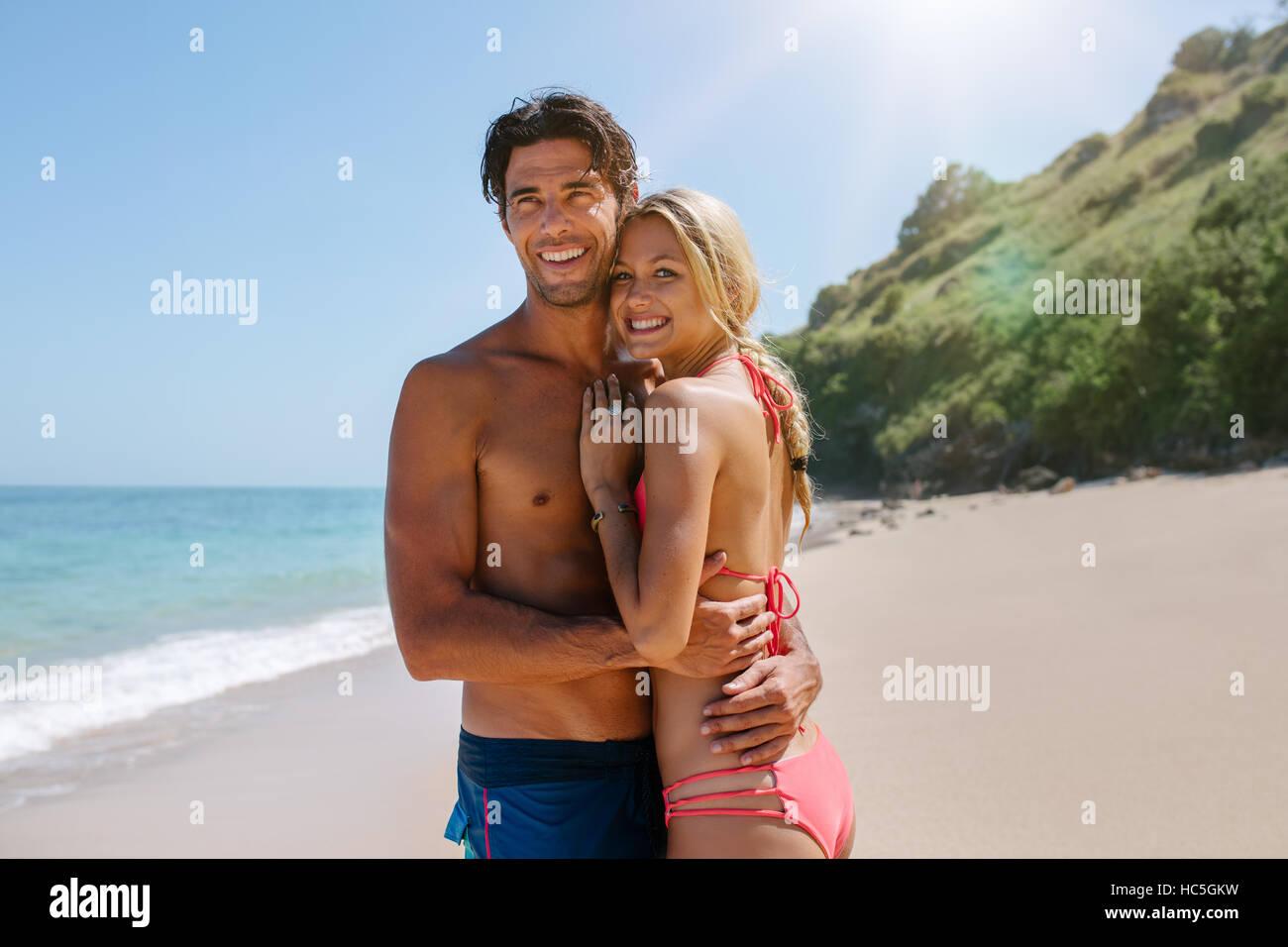 Couple aimant en maillot embrassant sur la plage. Jeune couple romantique sur la mer à la route et souriant. Banque D'Images