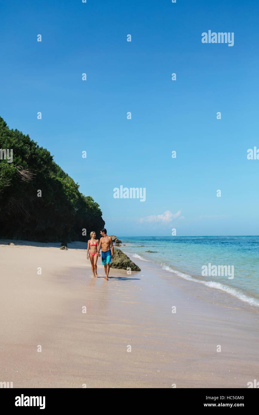 Coup de jeune homme et femme marche sur la côte tropicale. Jeune couple sur la plage, profitant des vacances d'été. Banque D'Images