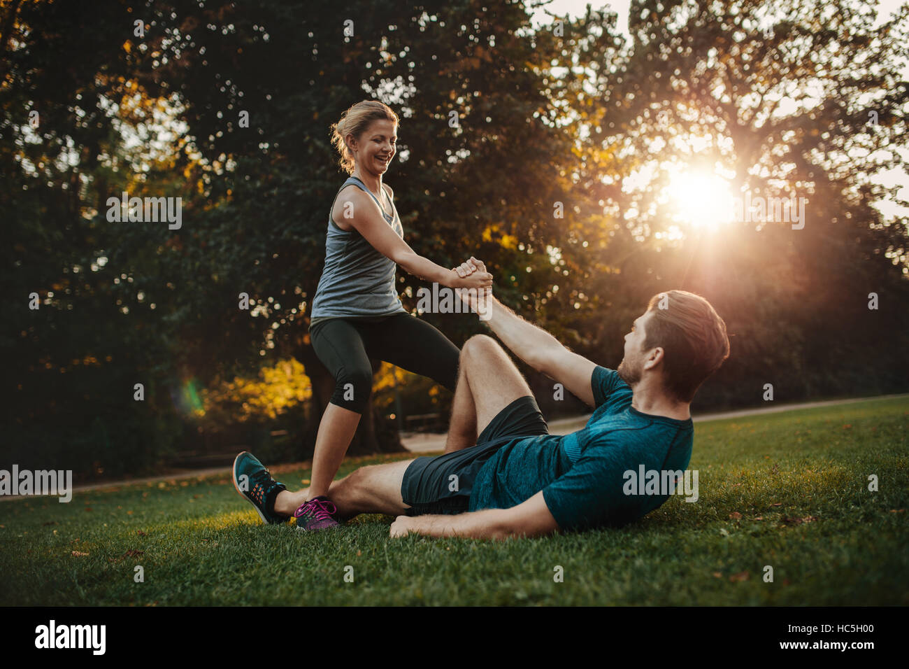 Coup de jeune femme d'aider l'homme à se lever de terre. Jeune couple à sain exercice du parc ensemble. Banque D'Images