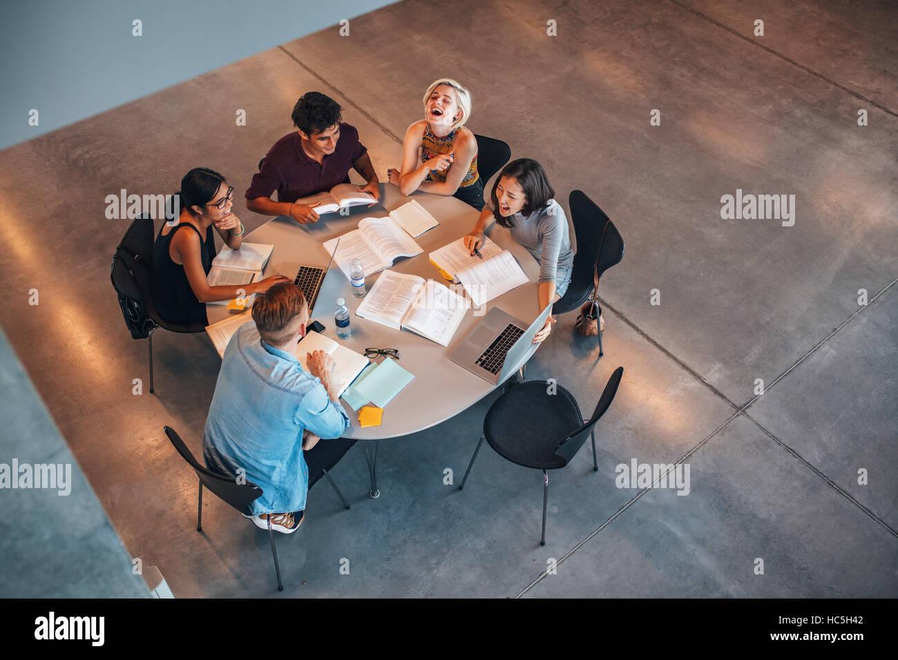 Vue de dessus du groupe d'étudiants assis ensemble à table. Les étudiants de l'Université d'étude de groupe et souriant. Banque D'Images