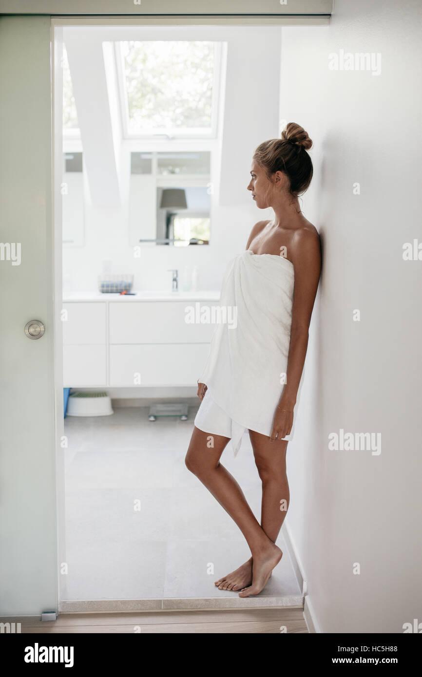 Full Length shot of young woman wrapped in towel debout dans la salle de bains à l'écart et la pensée. Femme après Banque D'Images