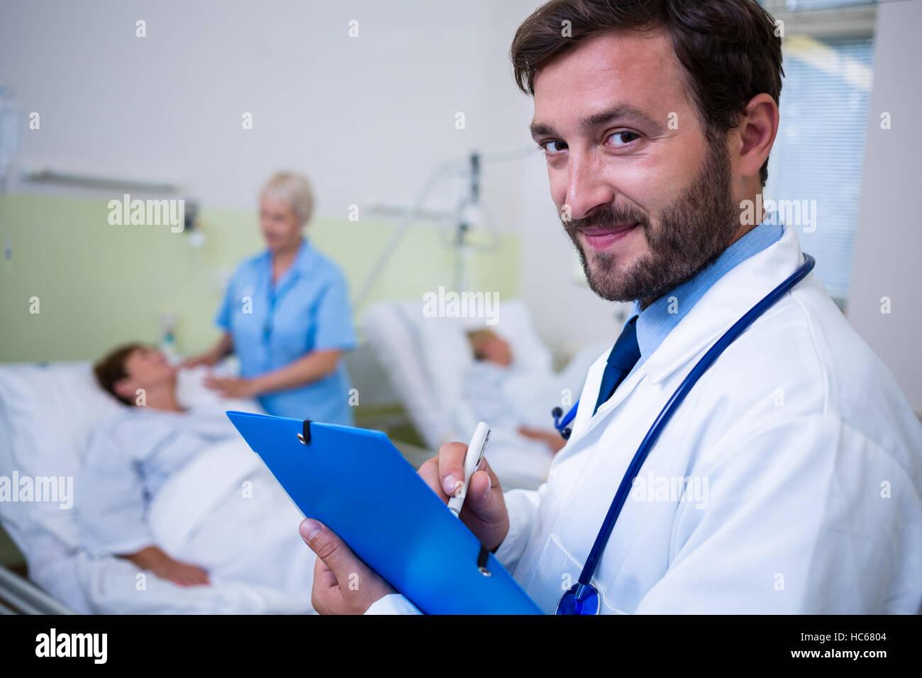 Portrait of smiling doctor vérification d'un rapport médical Banque D'Images
