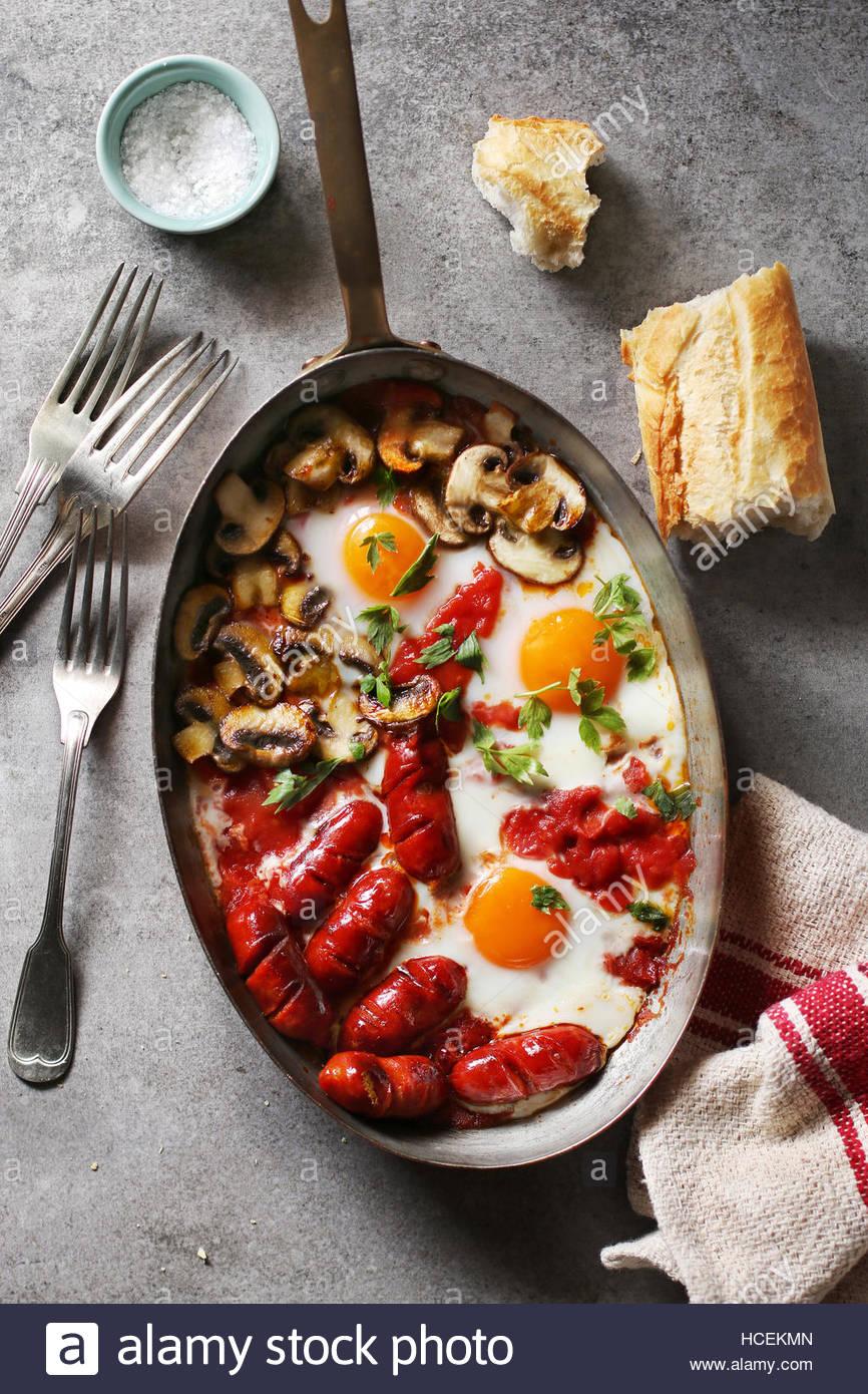 Oeufs cuits au four avec une sauce tomate, saucisses et champignons sur une casserole en cuivre.vue d'en haut Photo Stock