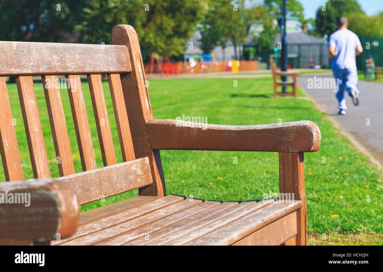 les banc en bois avec un jogger en arrière-plan dans un parc banque