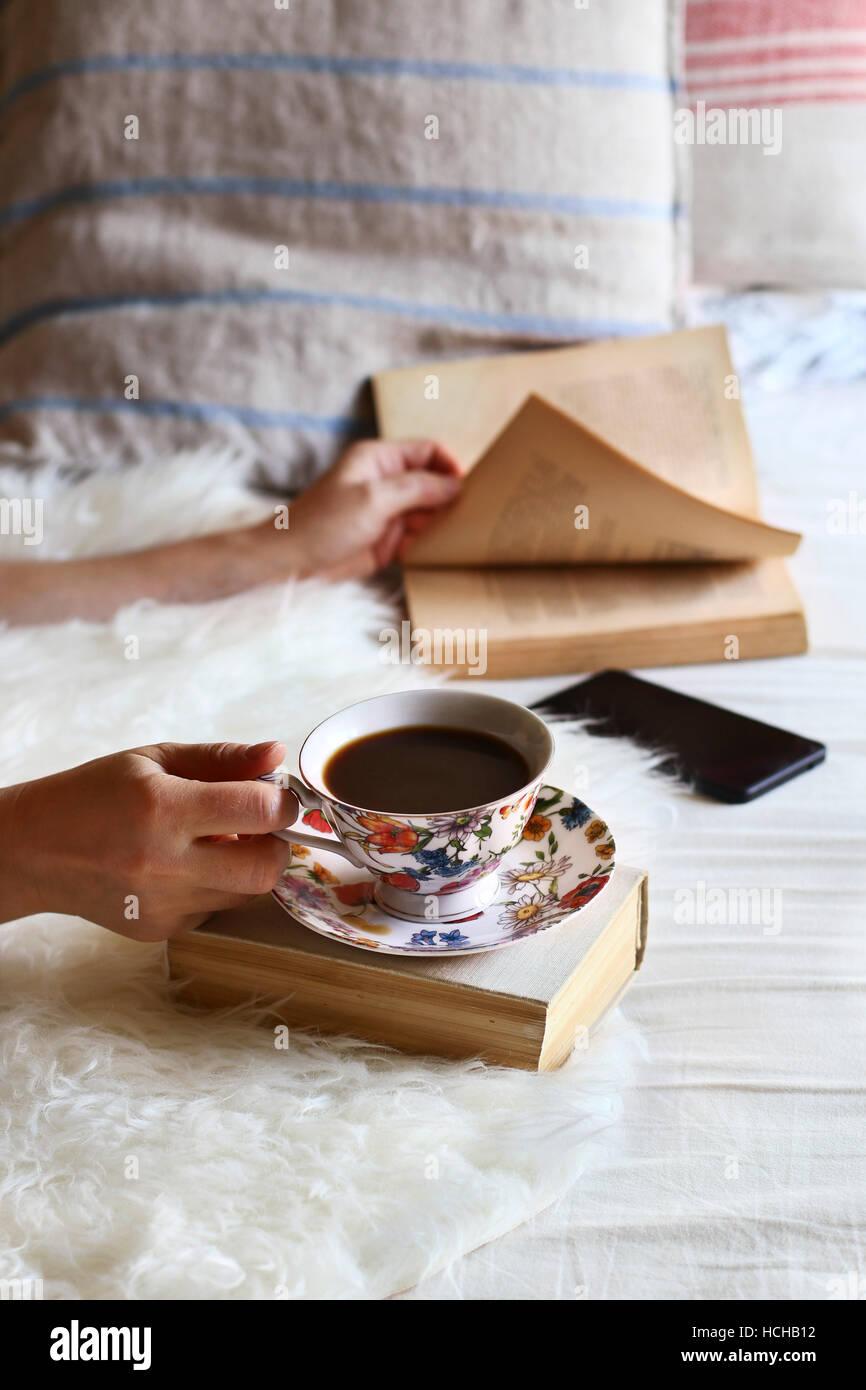 Femme assise sur le lit, feuilletant un livre et de boire une tasse de café. Photo Stock