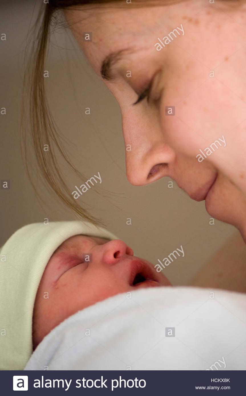 Jeune mère regarde affectueusement bébé nouveau-né fille. Photo Stock