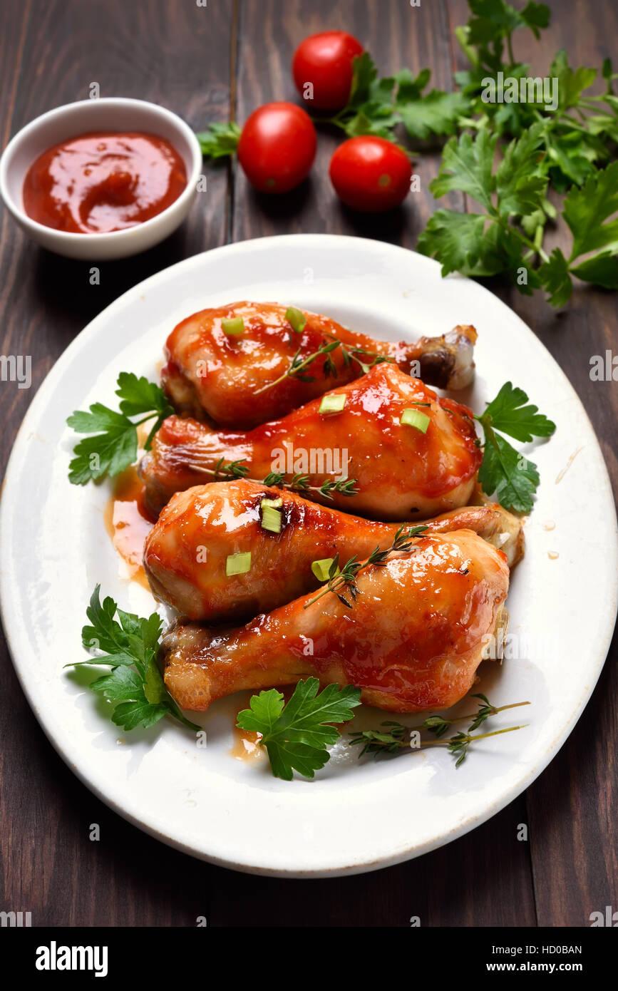 Pilons de poulet frit dans une sauce rouge Photo Stock