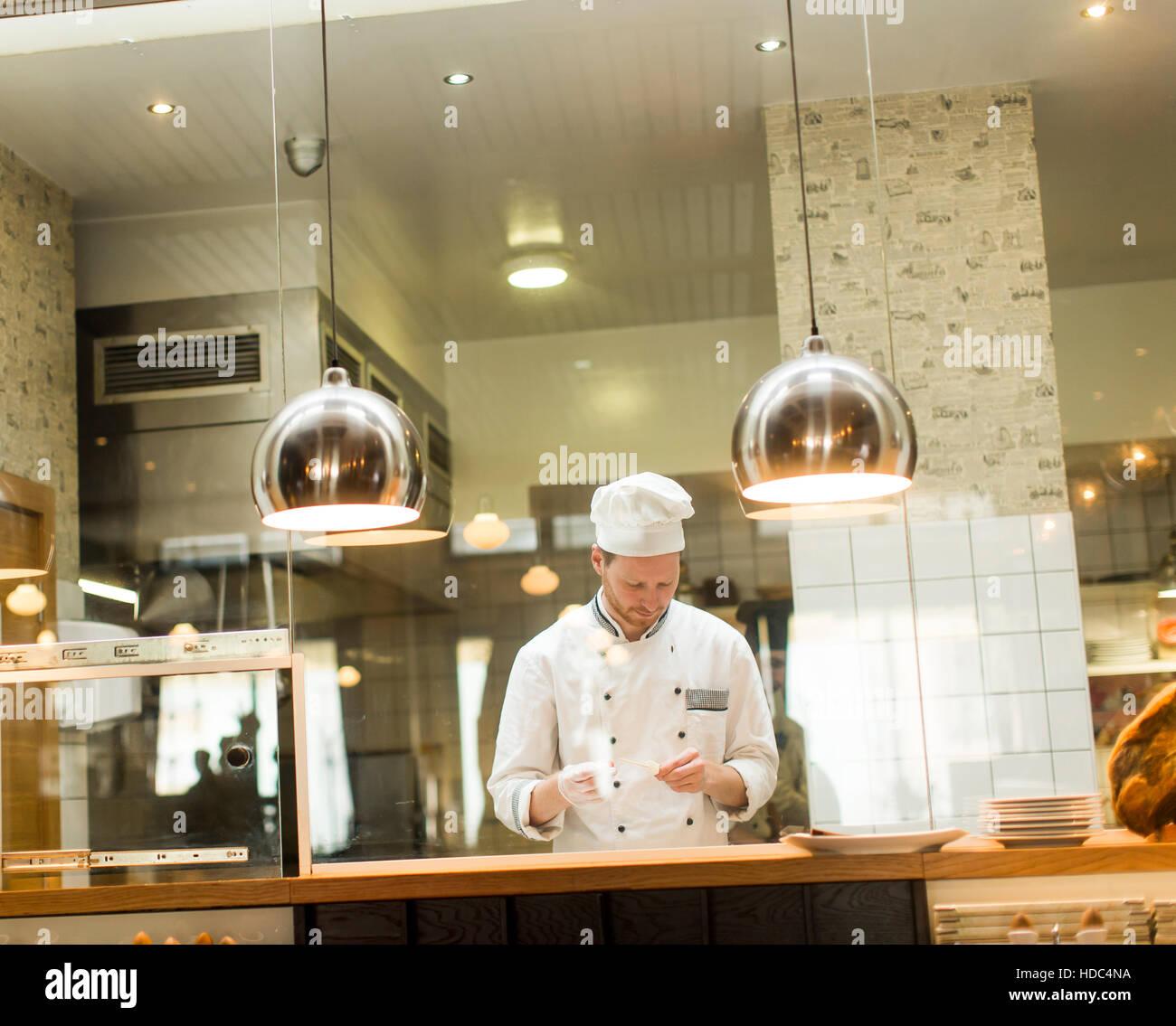 Jeune chef avec uniforme blanc debout à une cuisine moderne dans le restaurant et la préparation des aliments Photo Stock