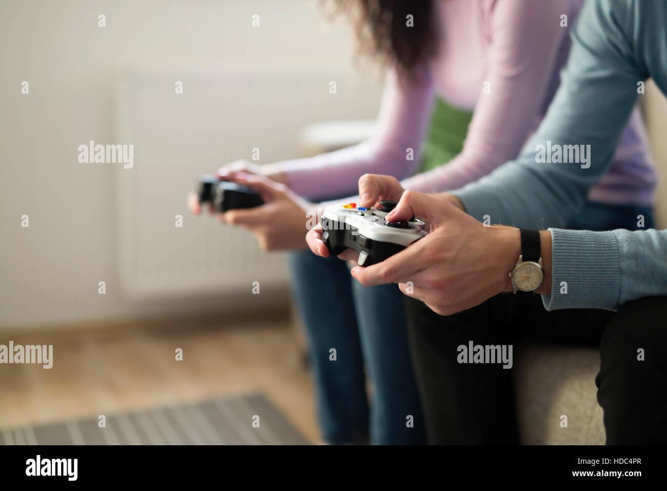 Les jeunes à jouer à des jeux vidéo sur les contrôleurs de la console Photo Stock