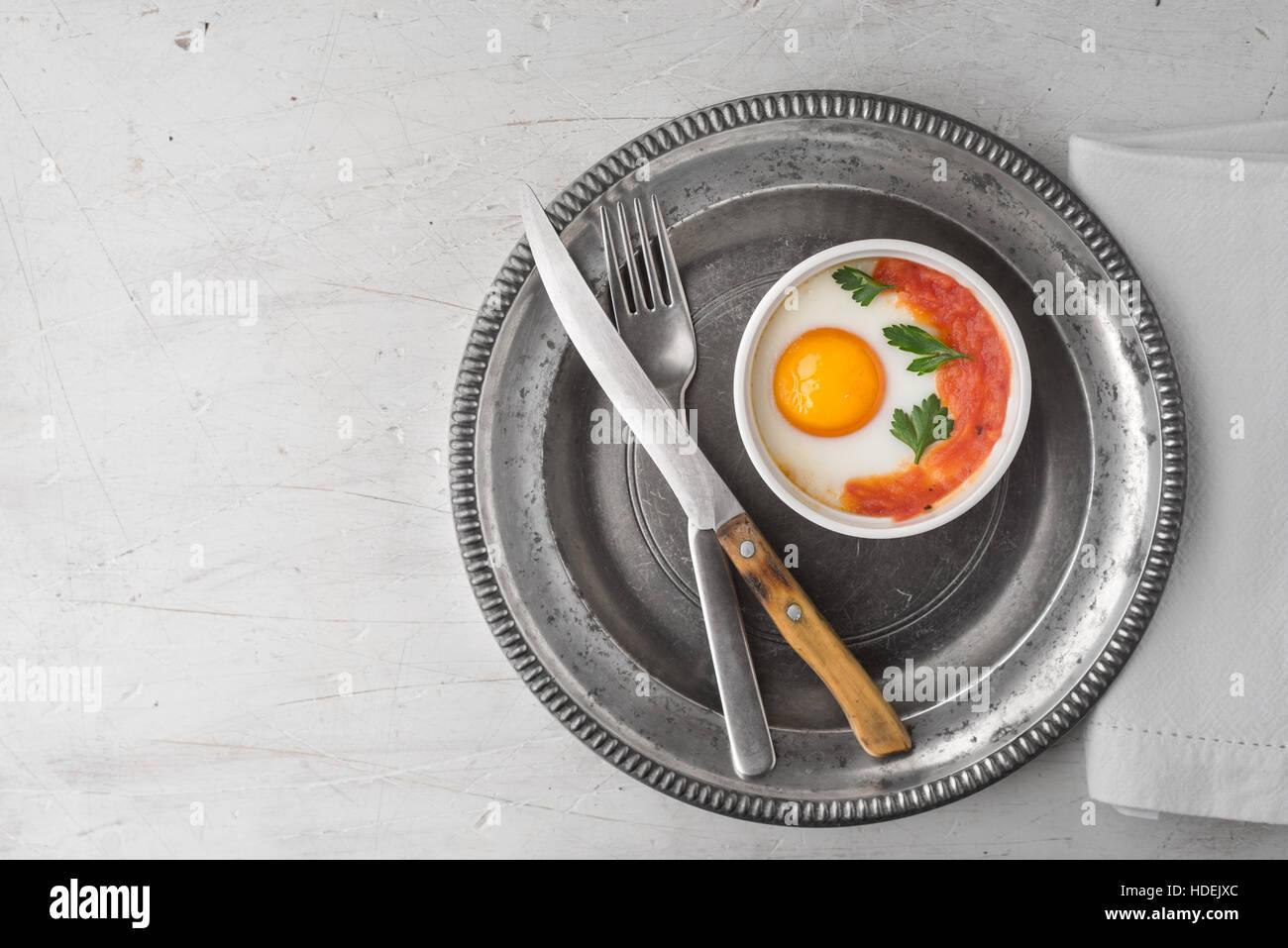 Oeufs cuits au four avec tomates et le persil dans les ramequins avec couverts vue supérieure Photo Stock