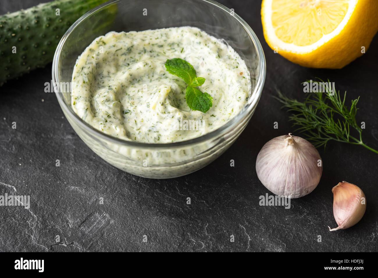 Sur Tzatziki la pierre noire avec des ingrédients de la table Photo Stock