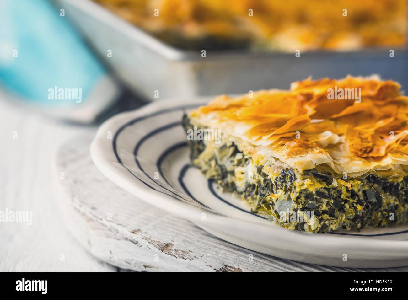 Spanakopita tarte grecque dans la plaque en céramique sur la table horizontale blanche Photo Stock