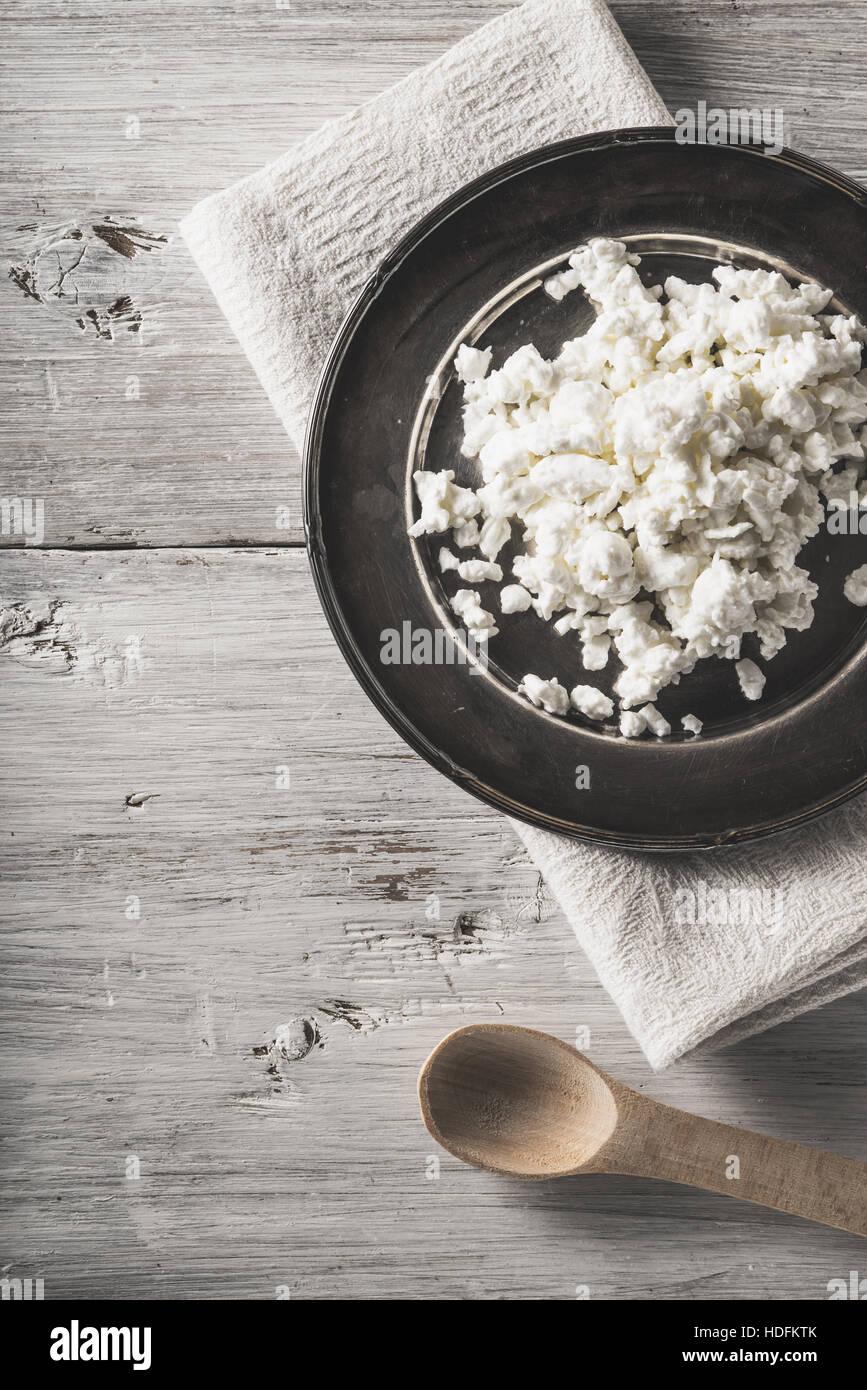 Le fromage cottage frais sur la plaque de métal sur la table verticale en bois blanc Photo Stock