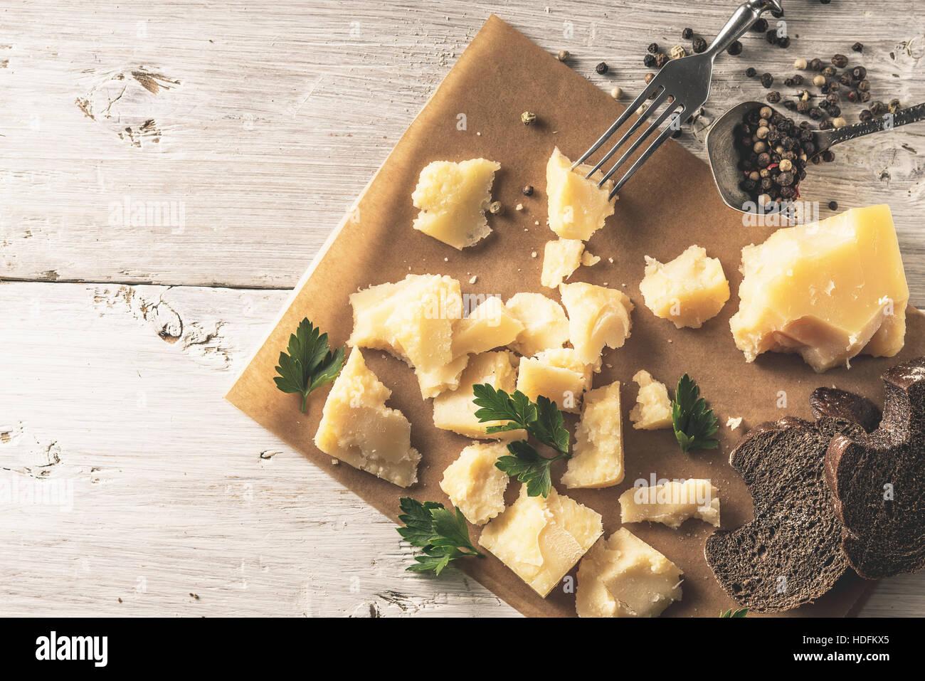Tranches de pain avec le parmesan , le persil et le poivre noir sur le parchemin sur la table en bois blanc Vue Photo Stock