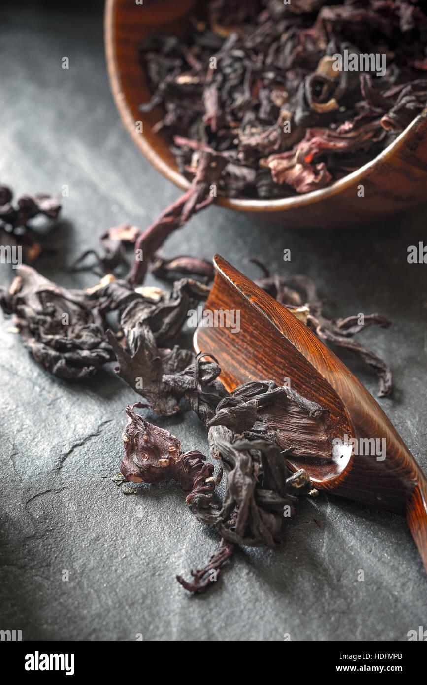 Hibiscus tea dans le bol en bois sur la pierre sombre table verticale Photo Stock