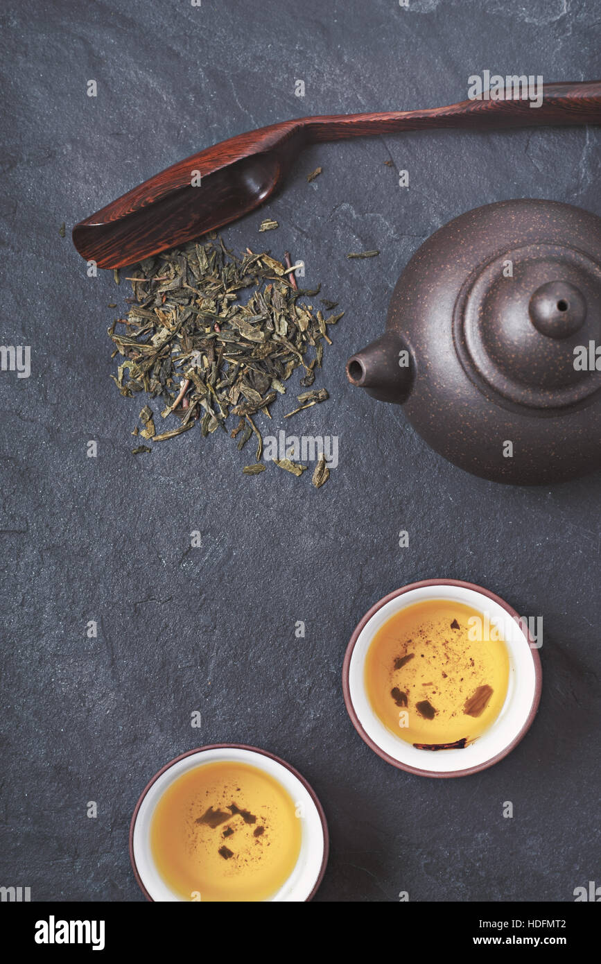 Théière chinoise et le bol avec du thé vert sur la pierre verticale en arrière-plan Photo Stock