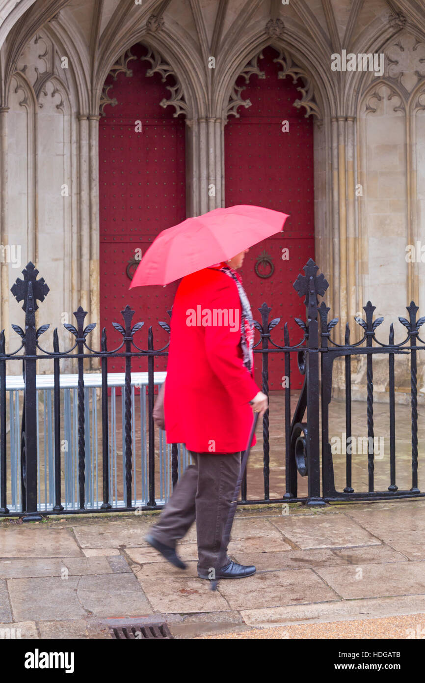Winchester, Hampshire, Royaume-Uni 12 décembre 2016. Lady se dépêche le long passé de la rue la cathédrale de Winchester en essayant de garder sec sous parapluie rouge sur un jour de bruine humide à la Winchester en décembre. Credit: Carolyn Jenkins/Alamy Live News Banque D'Images