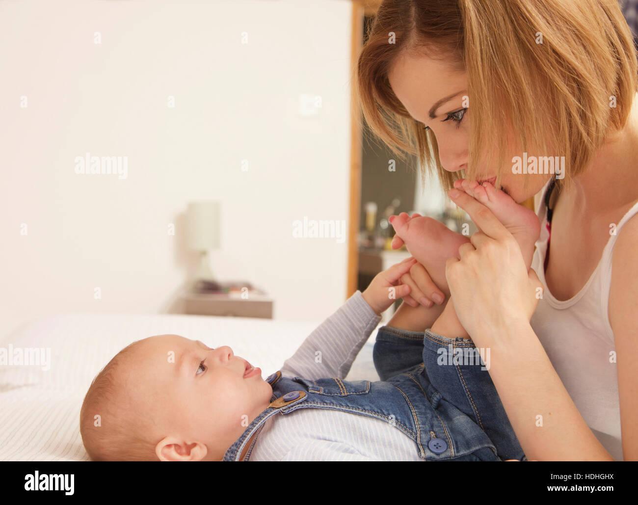 Loving mother kissing Baby Boy's foot à la maison Banque D'Images