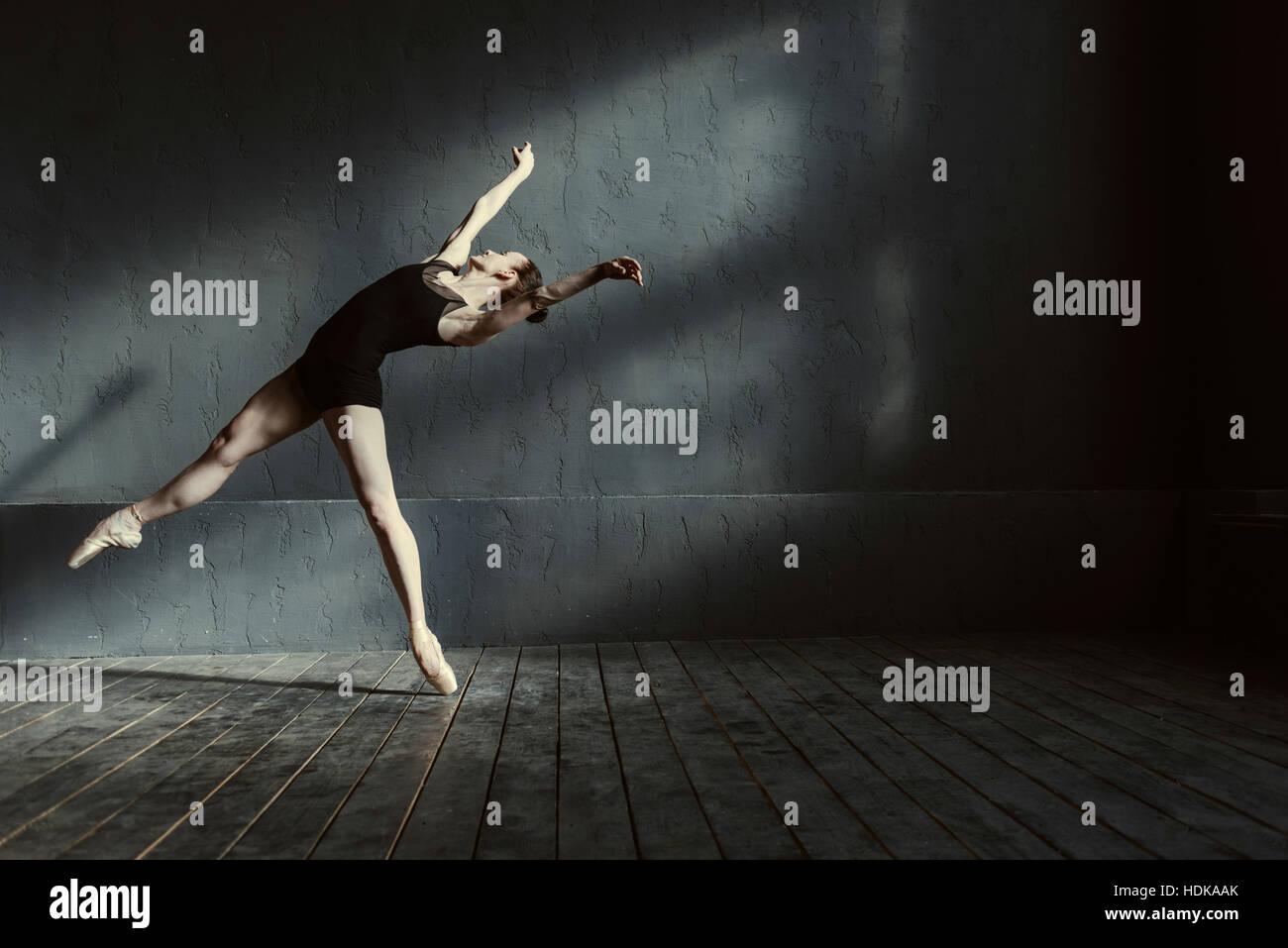 Les jeunes habile danseur de ballet agissant dans le pièce de couleur noir Photo Stock