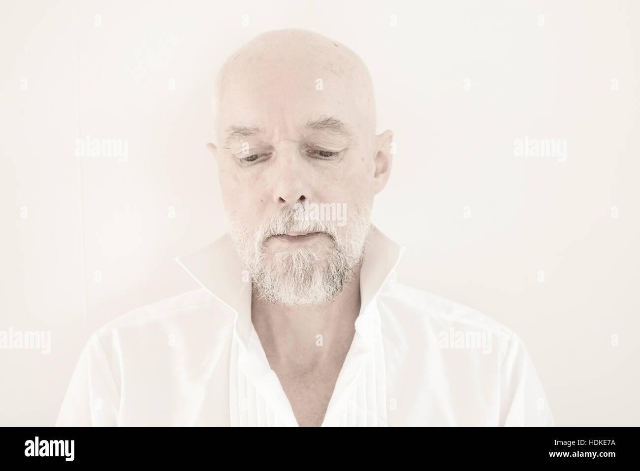 Triste et pensif old man looking down. Il porte une chemise déboutonnée blanche. Portrait de retraités de l'adulte Banque D'Images
