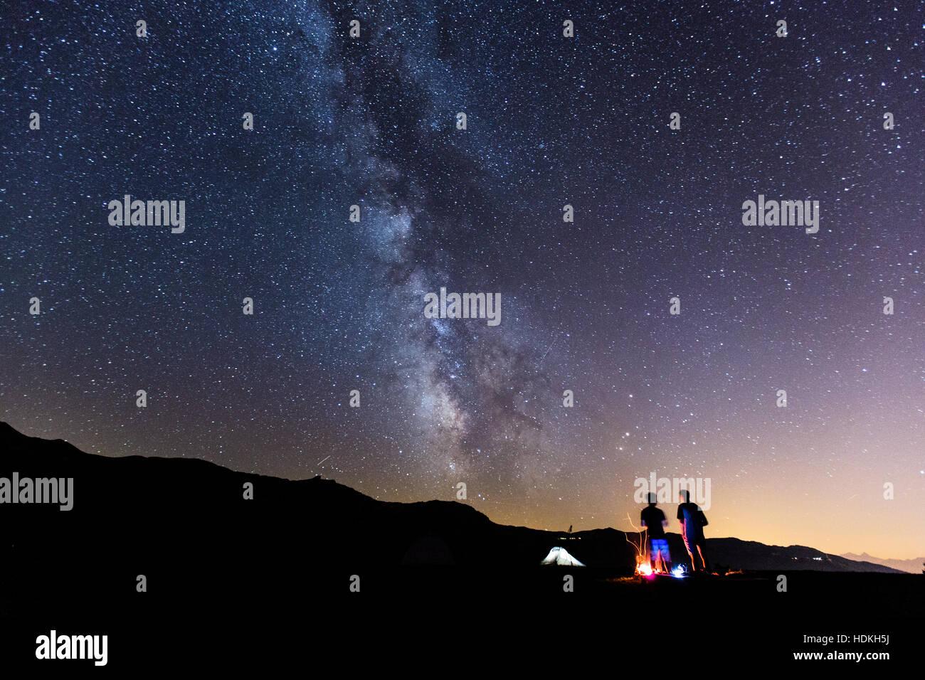 Voie lactée. Ciel de nuit avec des étoiles et silhouette de deux homme autour d'un feu Photo Stock