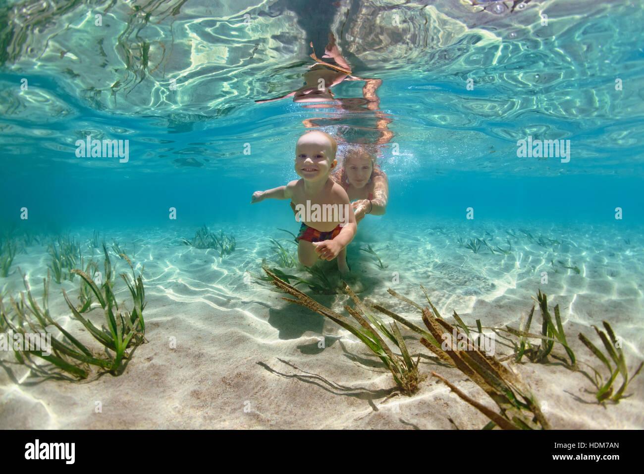 Happy Family - mère avec bébé nager, plonger sous l'eau avec piscine mer in. Membre actif de Photo Stock