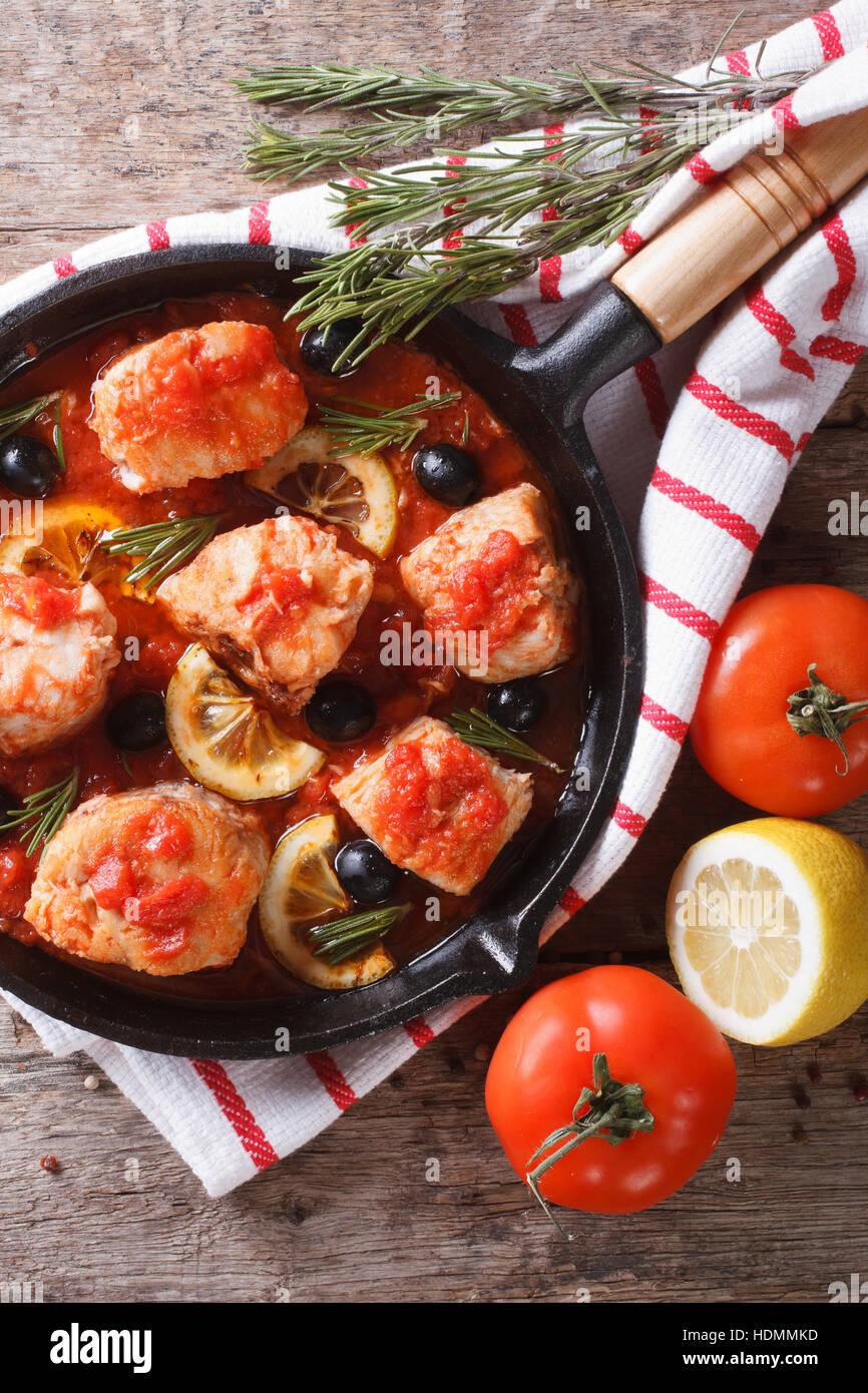 Poissons en sauce tomate aux Olives et citron dans une poêle. vertical vue d'en haut Photo Stock
