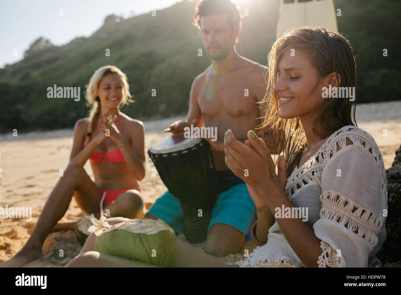 Jeune femme profitant des vacances avec ses amis sur la plage. Des mains des femmes et de l'homme jouant dumbek. Photo Stock
