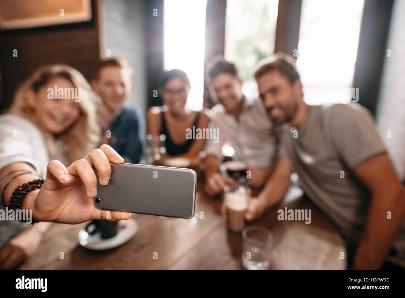 Groupe de jeunes de prendre un café à selfies. Jeunes amis au restaurant taking self portrait. Photo Stock